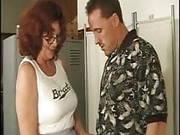 Rothaarige Alte mit Brille vernascht einen Mann in der Umkleidekabine